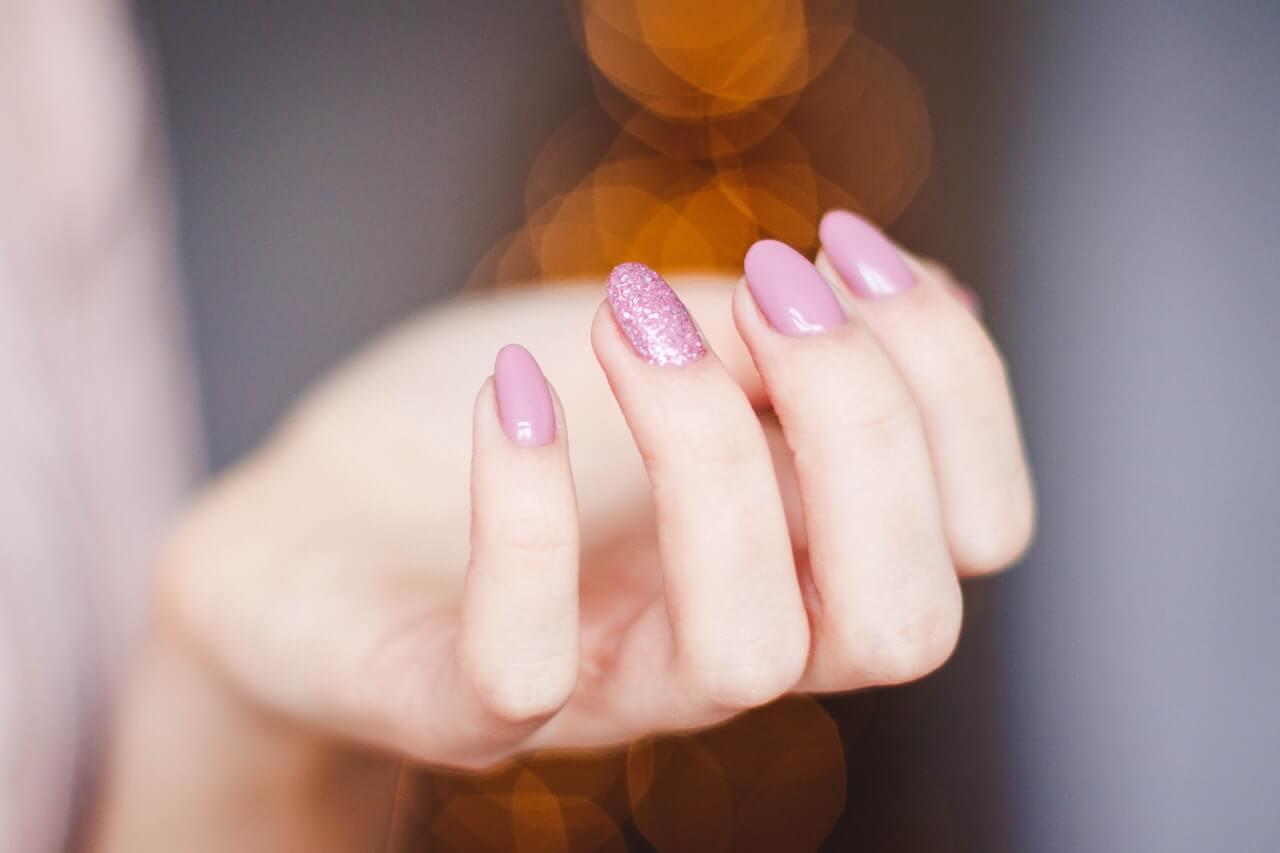 Kobieca-dlon-z-pomalowanymi-paznokciami-na-rozowo