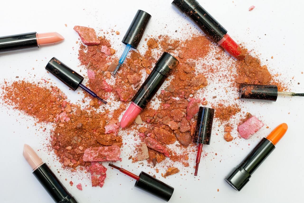 Kosmetyki-rozrzucone-i-rozsypane-na-bialym-tle