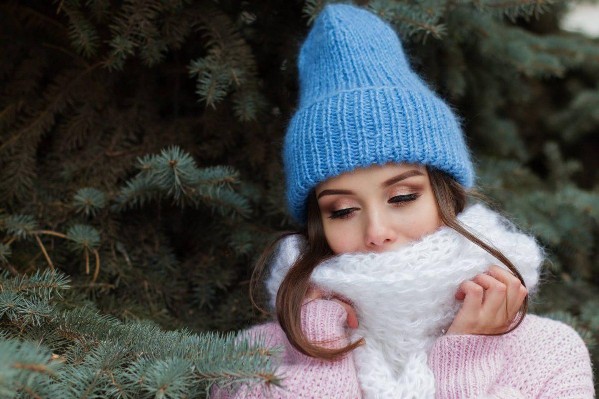 Dziewczyna-w-czapce-i-szaliku-na-tle-choinki