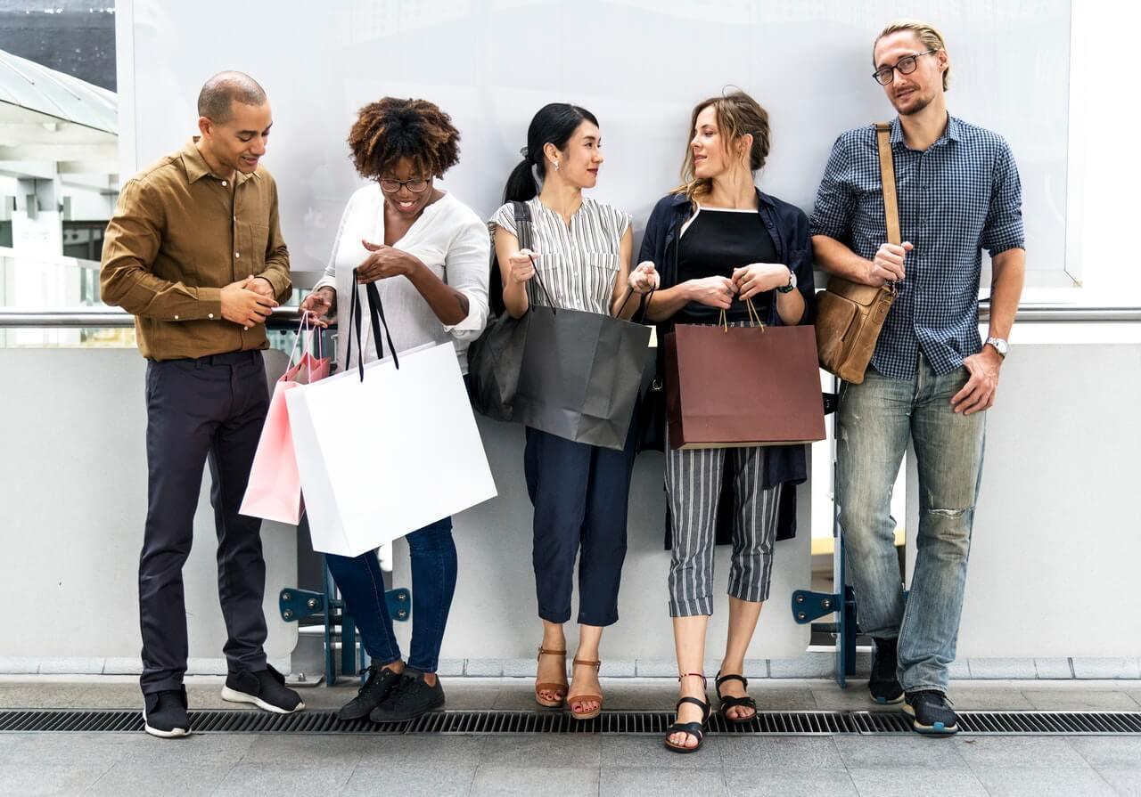 Grupka-ludzi-na-tle-sciany-z-torbami-na-zakupy