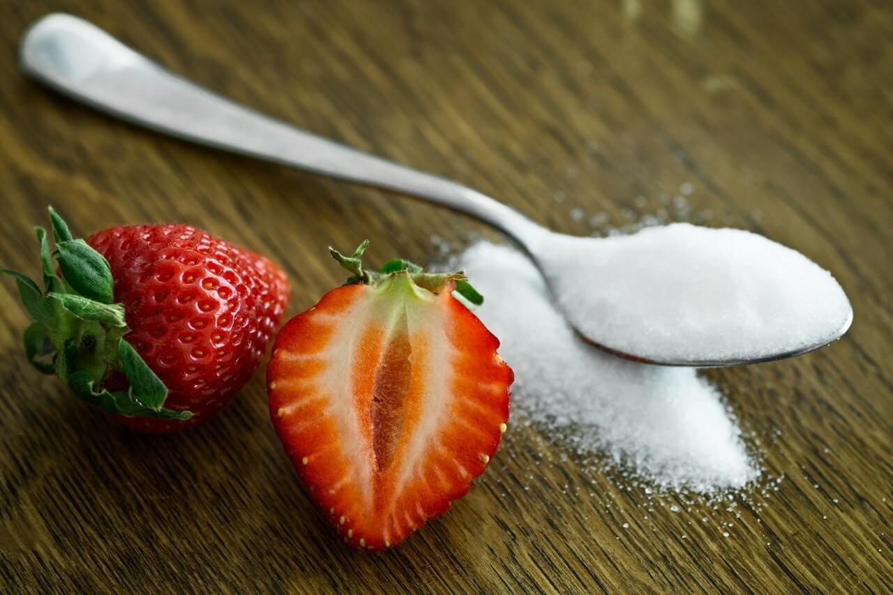 Lyzeczka-cukru-z-truskawkami-lezace-na-stole