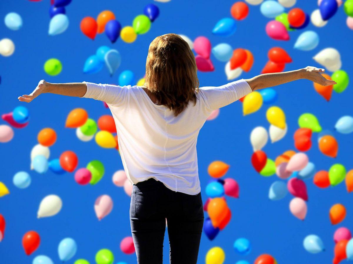 Kobieta-z-otwartymi-ramionami-na-tle-balonow
